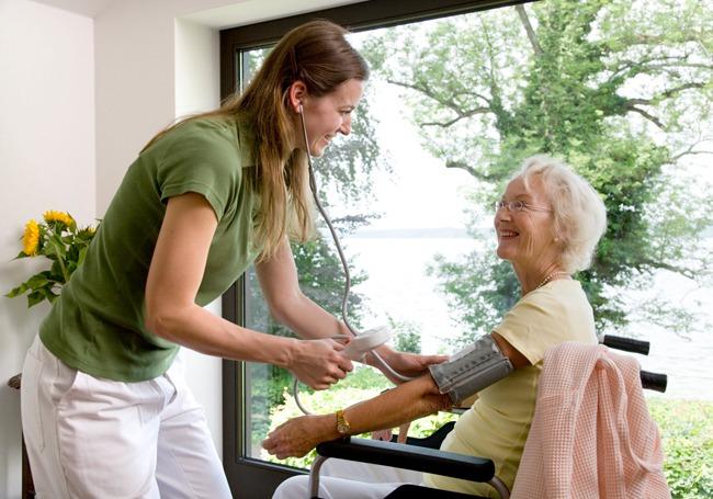 Medical healthcare expert taking blood pressure reading of elderly care home resident