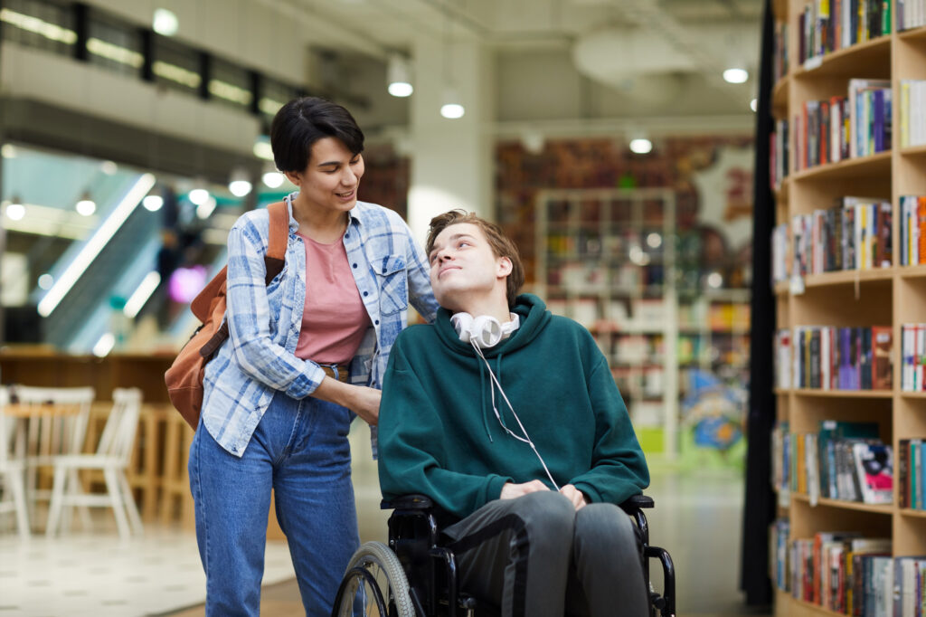 Carer and service user in wheelchair visiting library