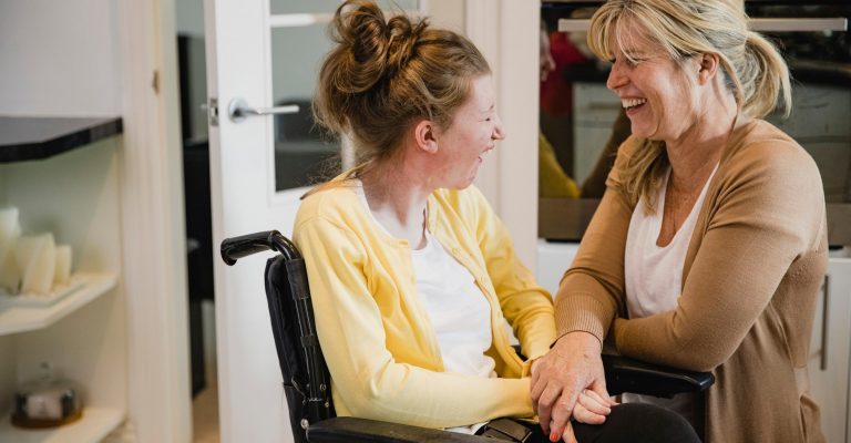 Carer and young person with learning disabilities sitting and laughing in wheelchair